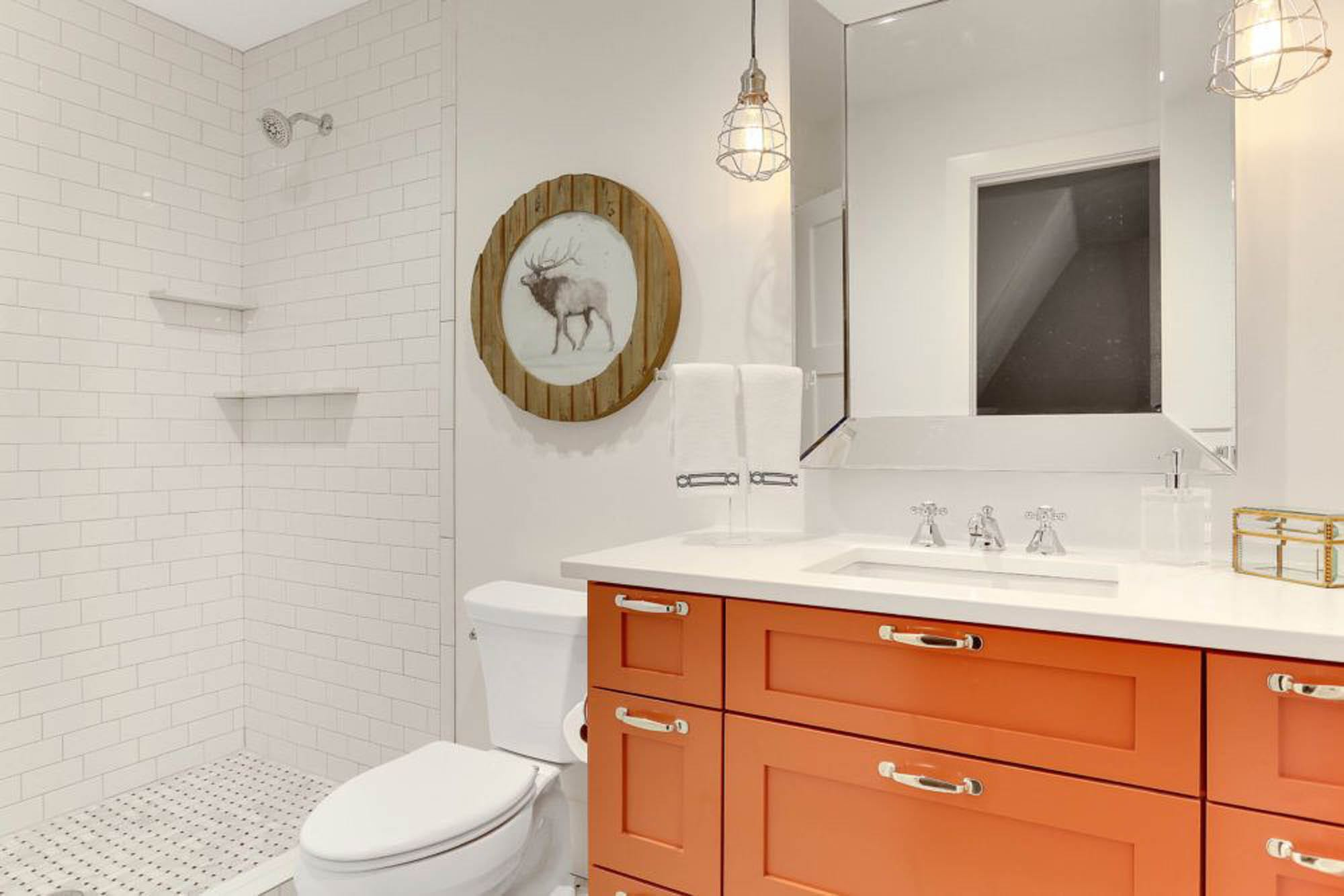 A pop of orange in a white tiled bathroom