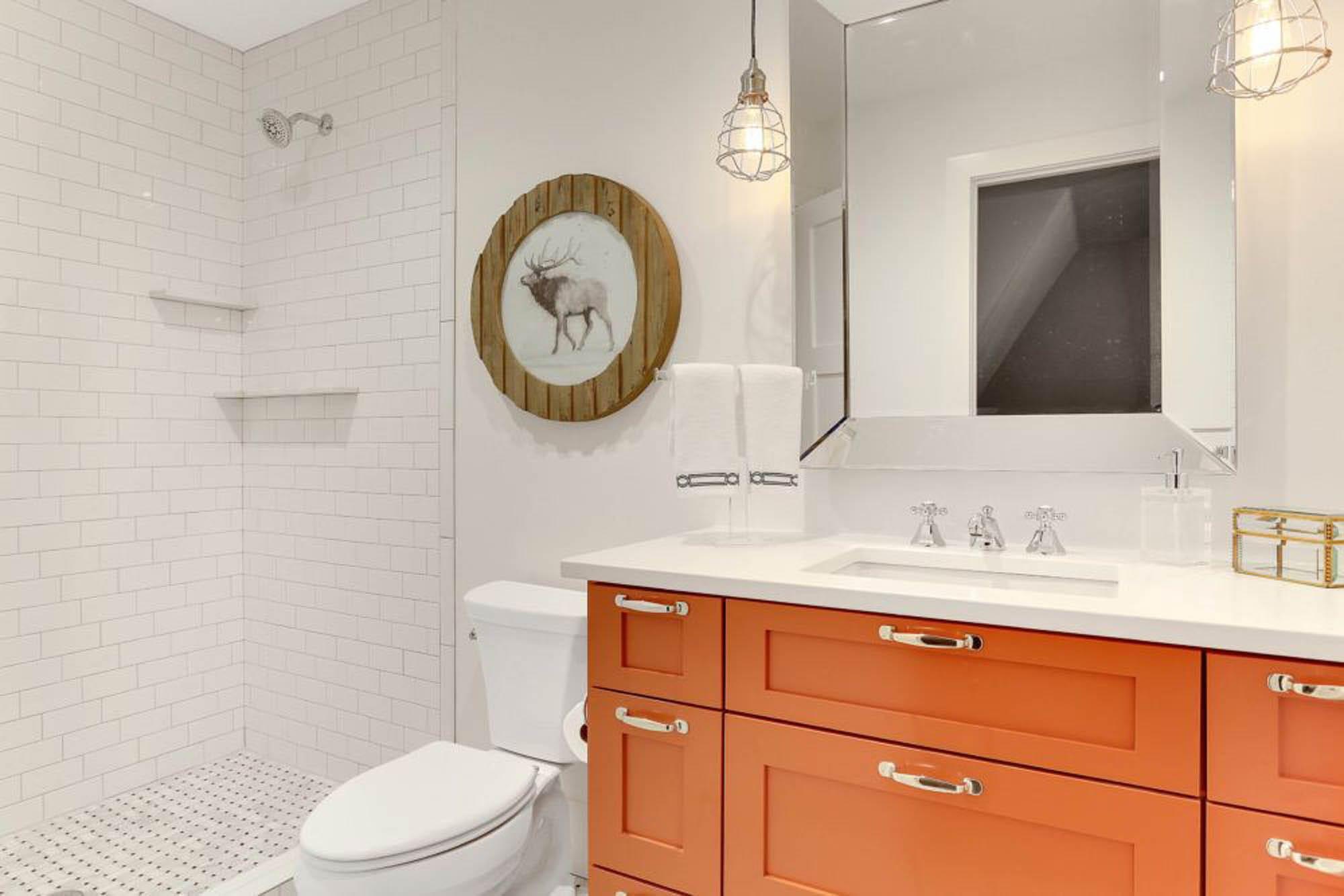 A pop of orange in a white tiled bathroom