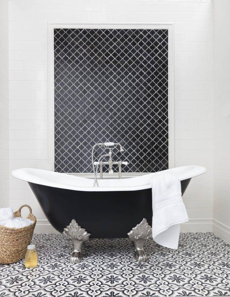 A black-and-white bathroom with an encaustic patterned floor.