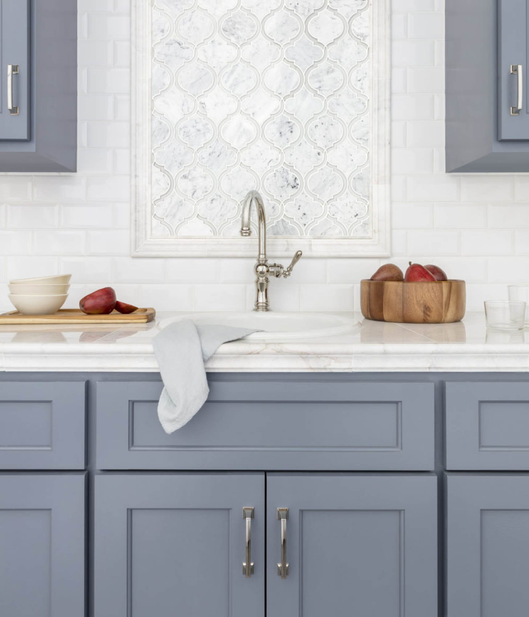 White wall tile and contrasting blue cabinets.