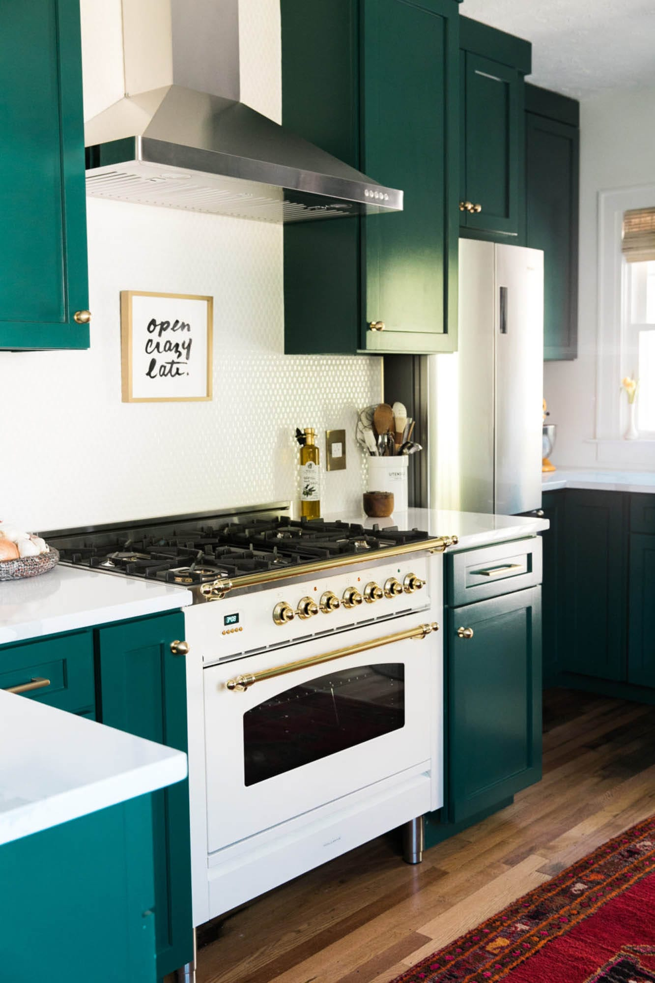 Green cabinetry and white penny round tile