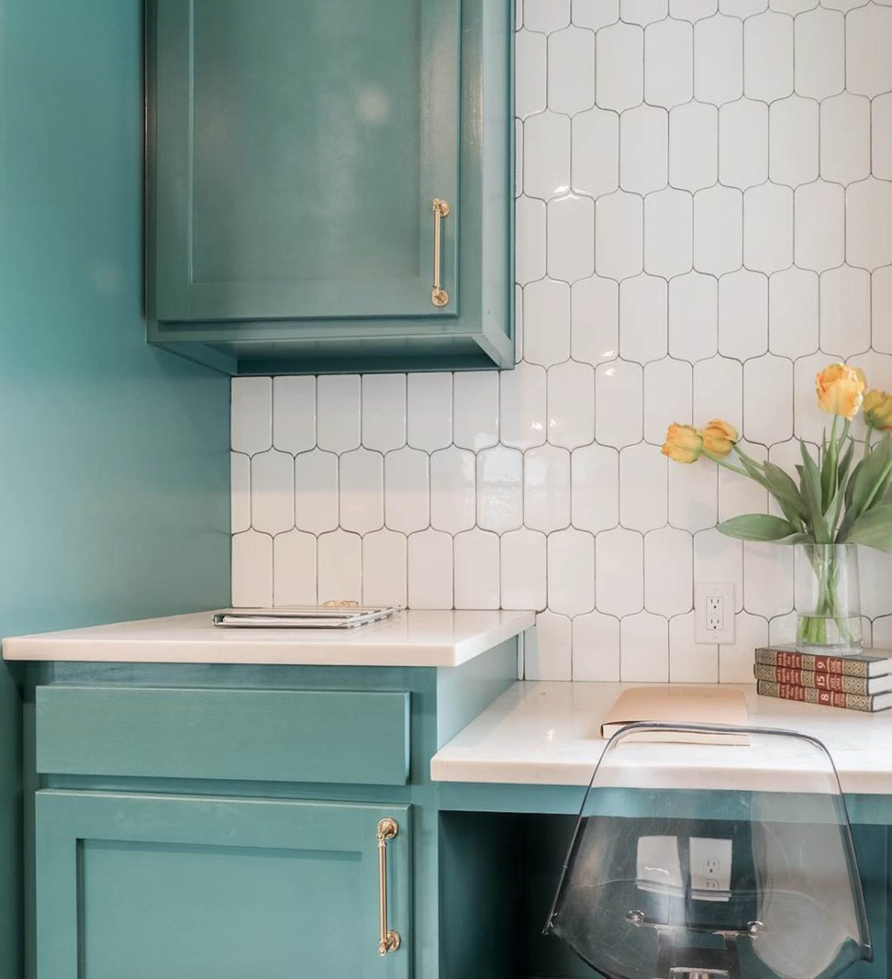 Turquoise cabinets and white backsplash tile
