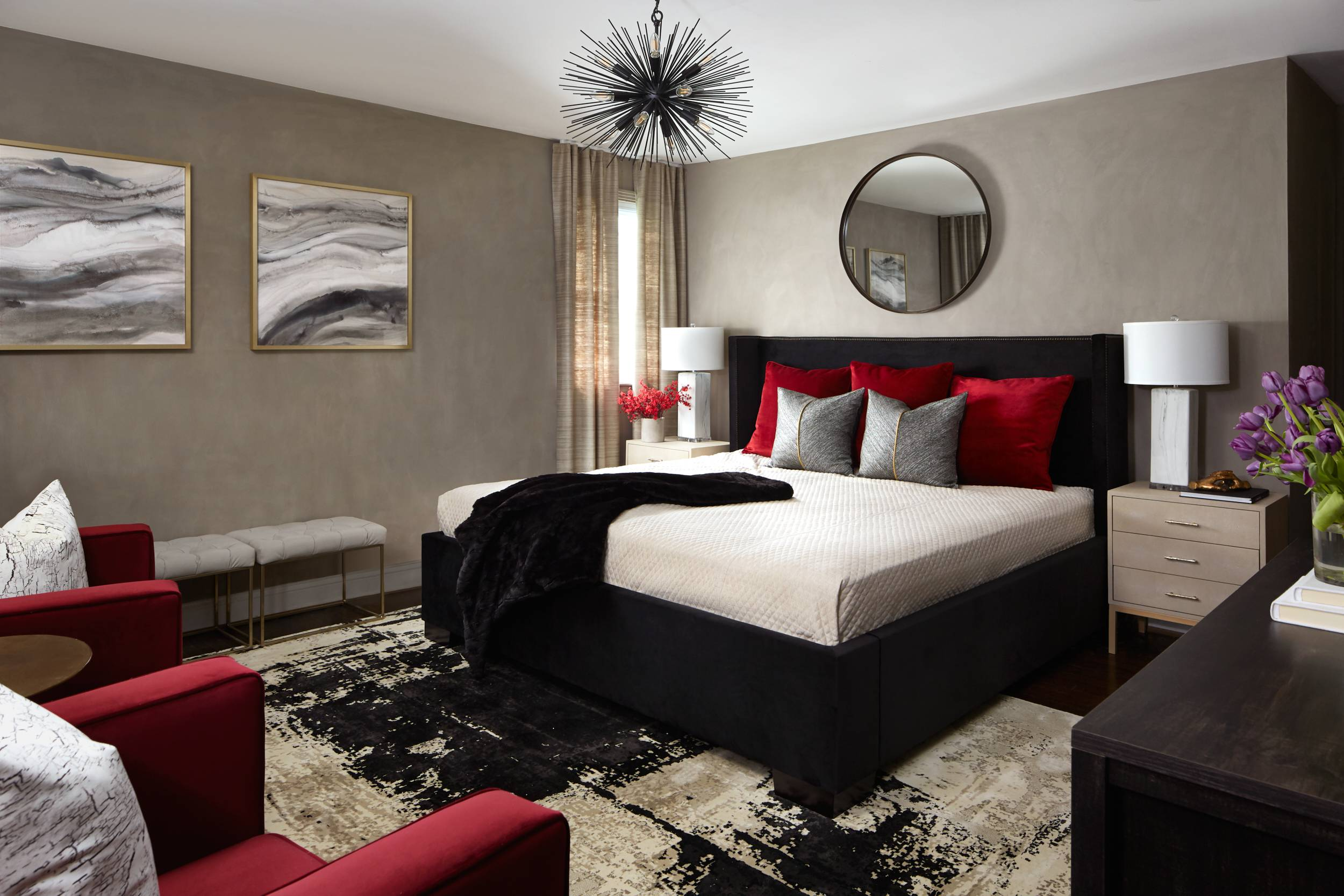 beige primary bedroom with black and red decor