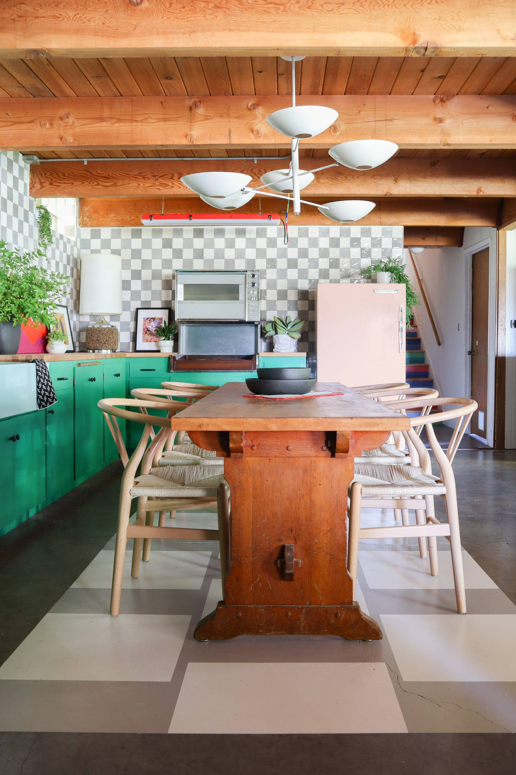 colorful kitchen and dining space with checkerboard tiled backsplash and green cabinets