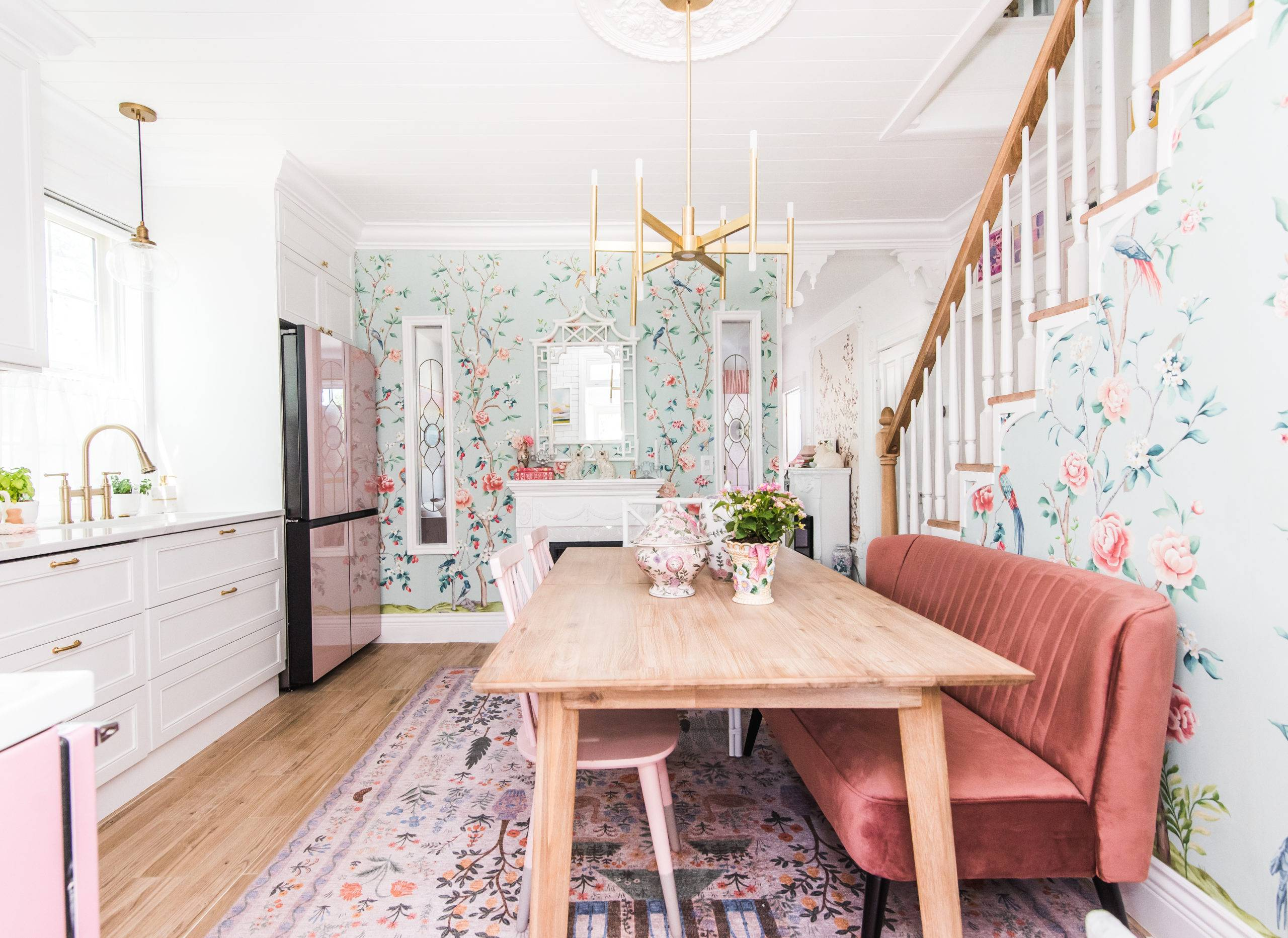 bright white kitchen and dining area with teal floral wallpaper and large wooden dining table