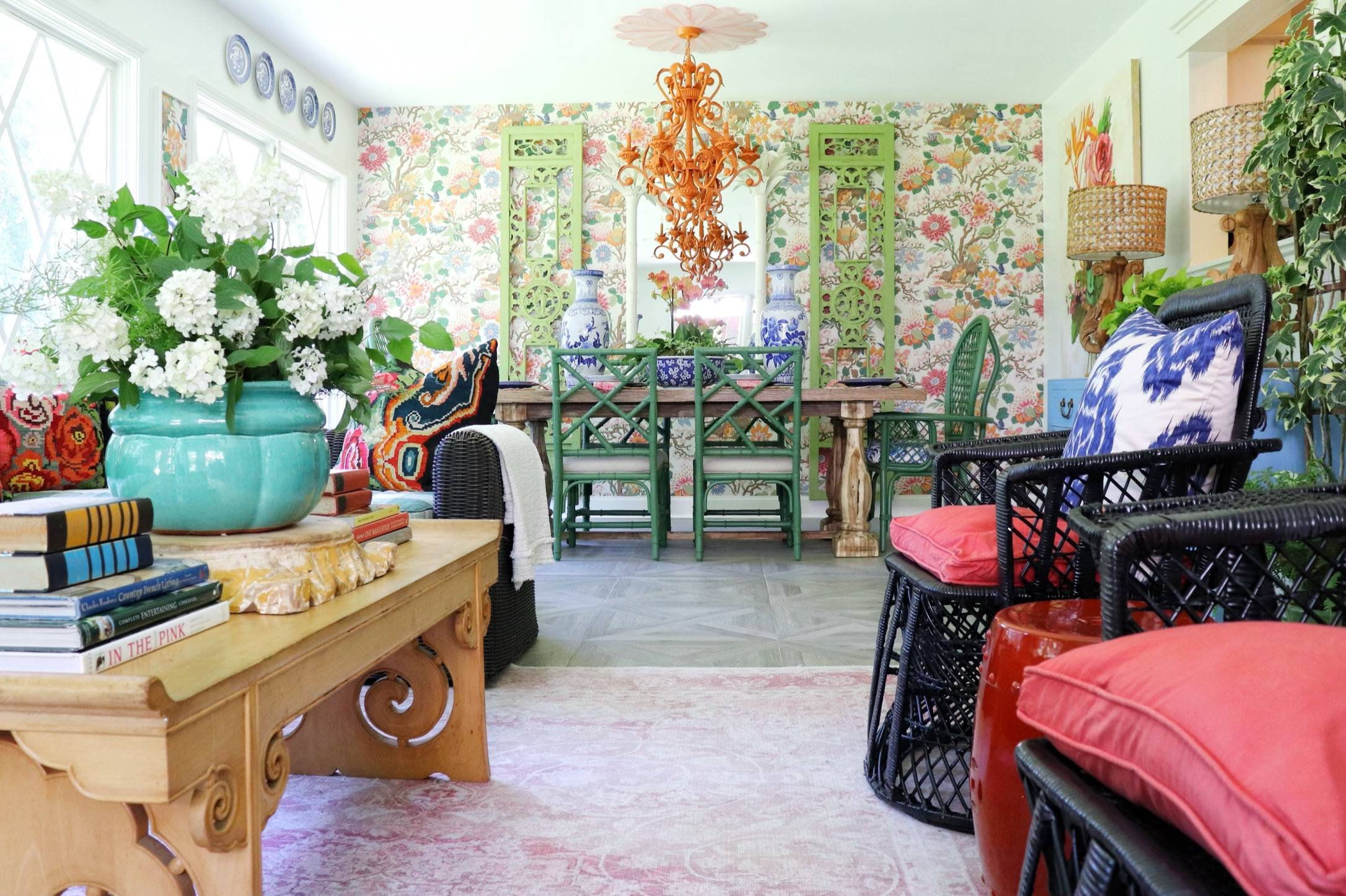 view of updated dining and living area with colorful floral wallpaper and an orange chandelier