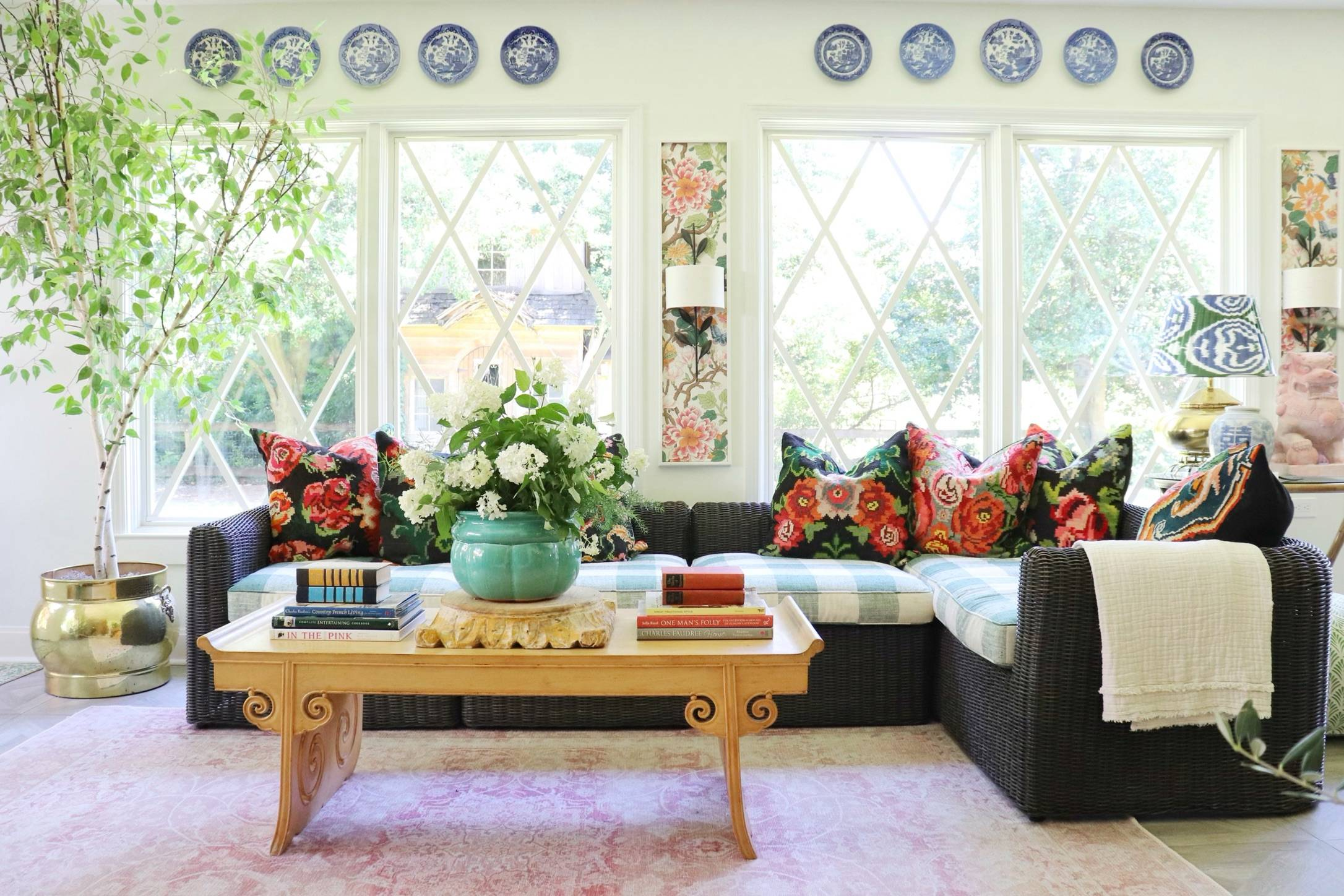 white living room with black wicker couch and floral decor