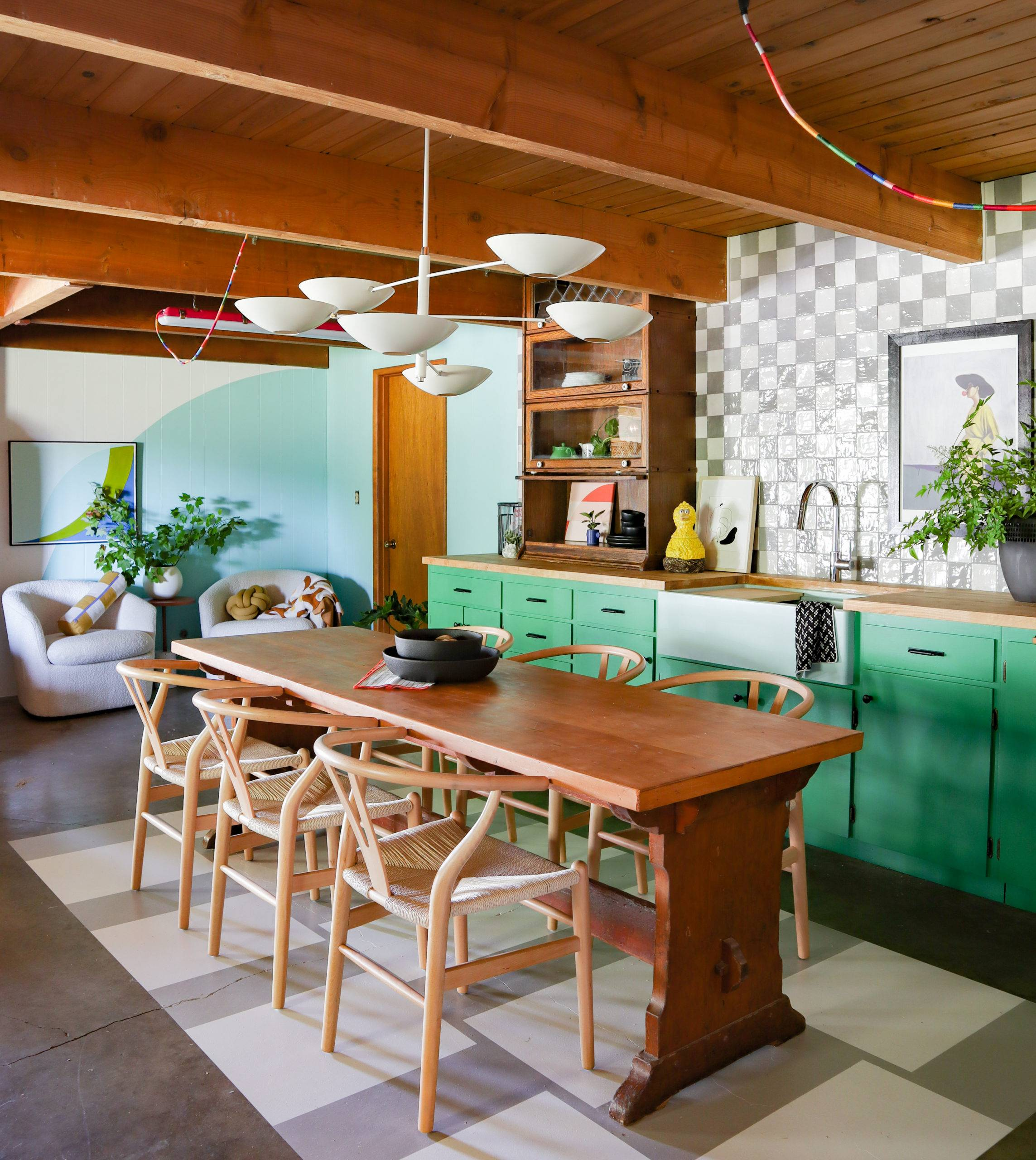 colorful kitchen with checkerboard tiled backsplash and wooden dining set