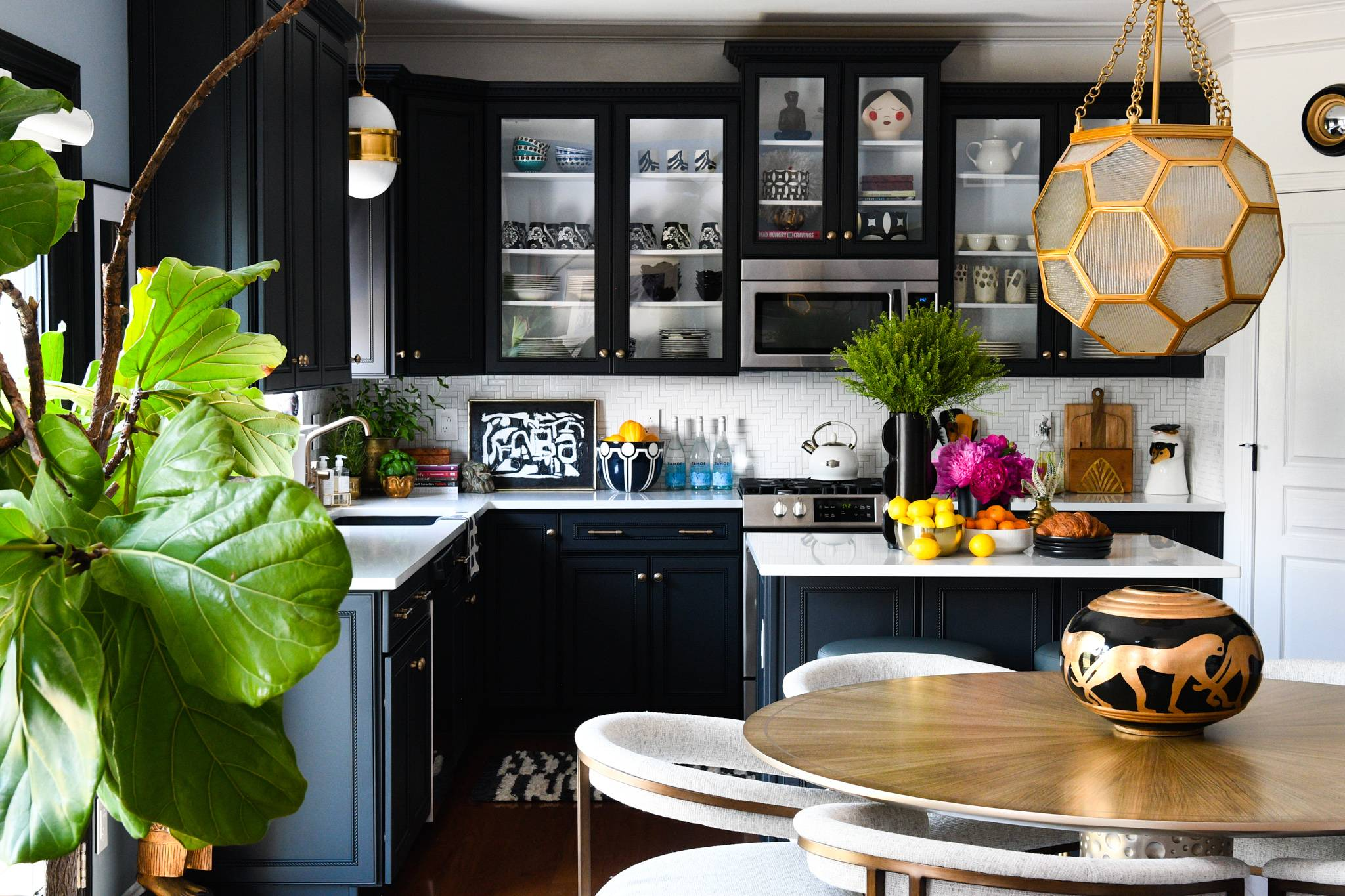 modern kitchen with black cabinets and white herringbone tiled backsplash