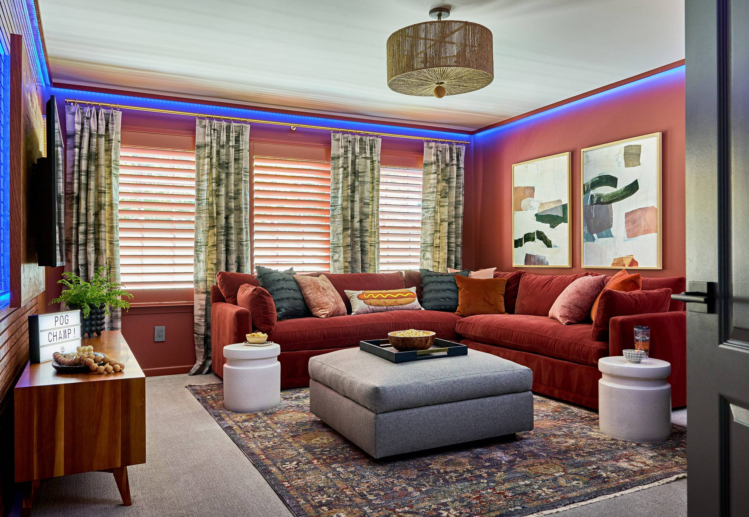 red game room with large couch and neon lighting